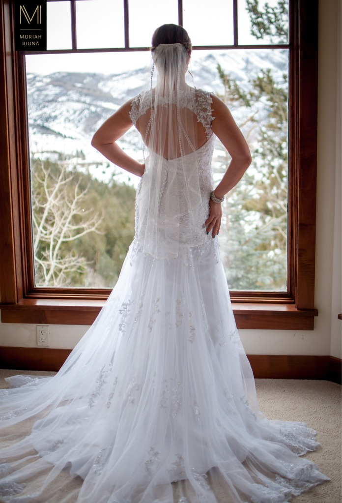 Bride standing in front of window with view of snowy Colorado mountains | © Moriah Riona, 2016