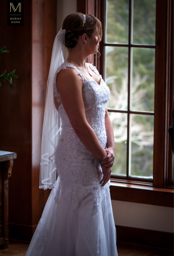 Beautiful bride stares out window of Colorado mountain home | © Moriah Riona, 2016