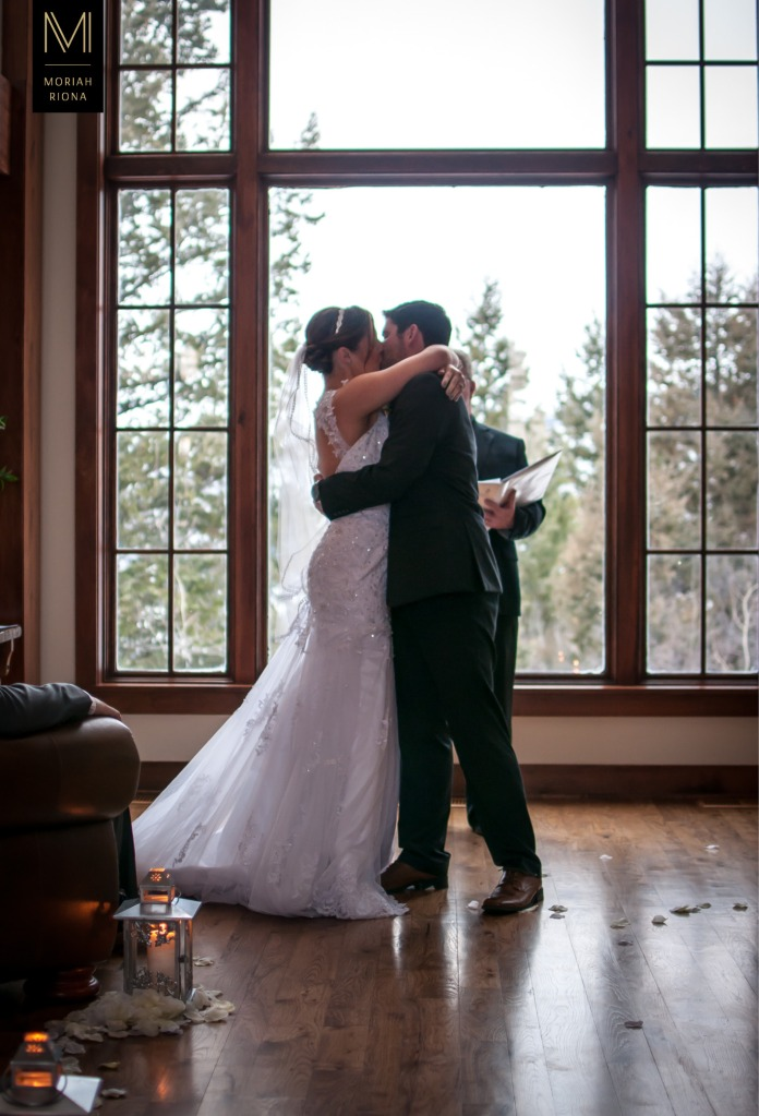 First kiss of bride and groom at intimate mountain ceremony | Photography by Colorado photographer, Moriah Riona