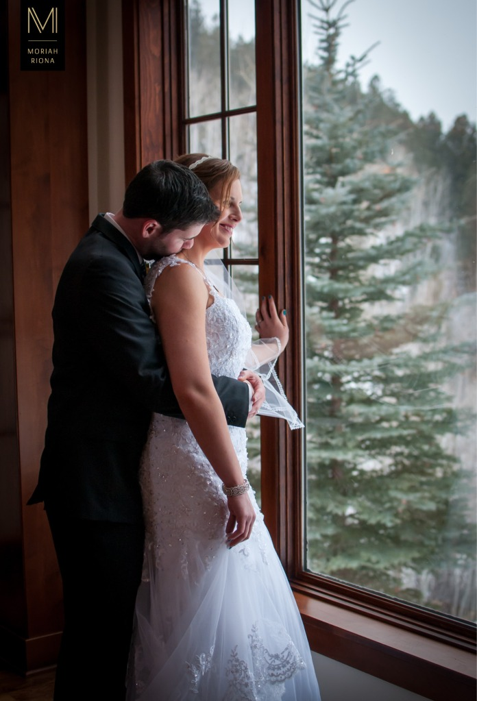 Bride and groom in front of window overlooking the Colorado Rockies at Winter Wedding | Photography by Colorado Springs photographer, Moriah Riona